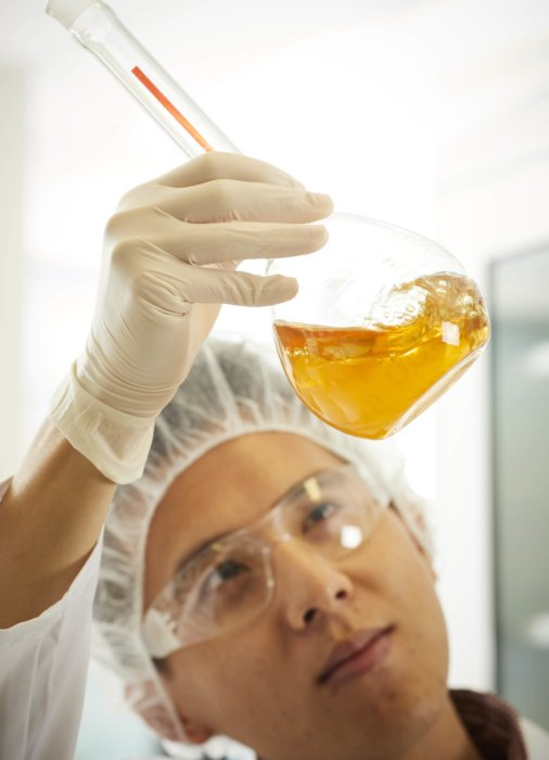 A man looking at and mixing up amber liquids | Healthcare Photographer