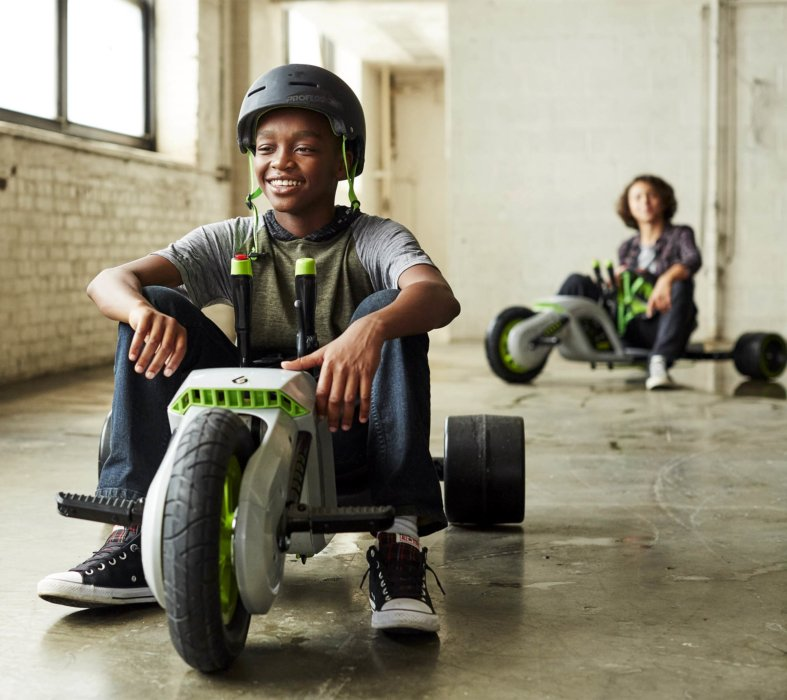 Two young kids riding cook tricycles in a warehouse