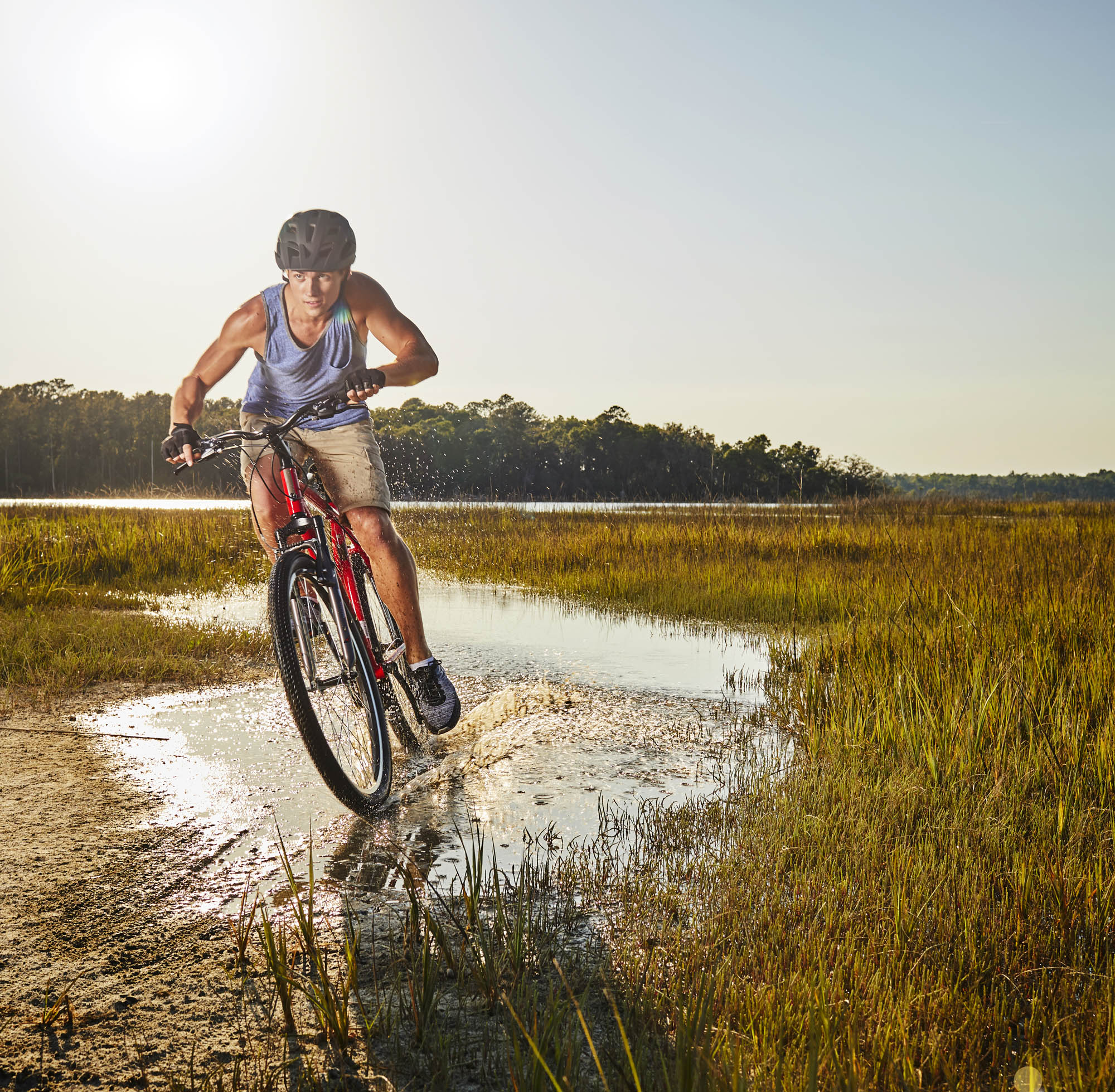 A young athletic man riding a bike through a wetland