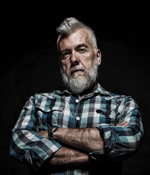 A portrait of a older rugged man with a bold beard and hair style