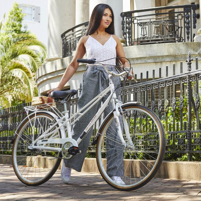 A product shot of a bike being walked by a young woman on a beautiful street