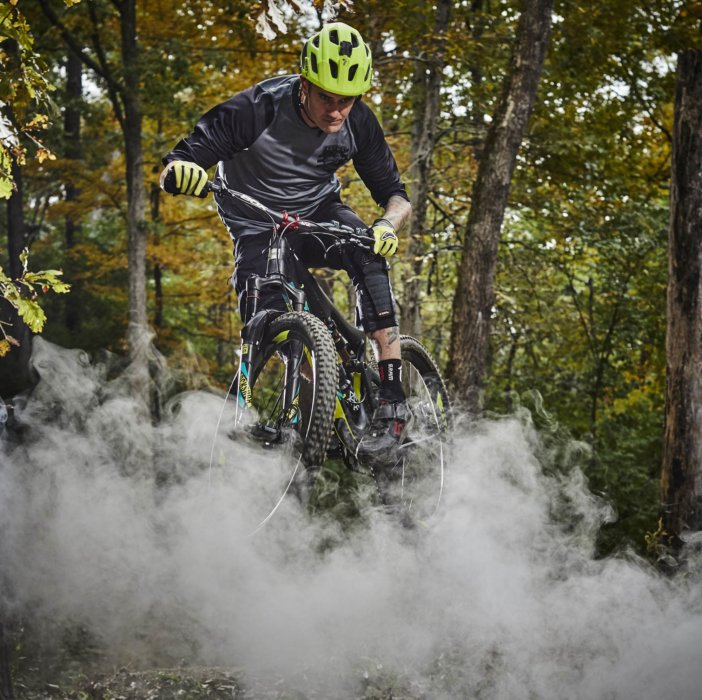 A biker jumping through smoke in the woods