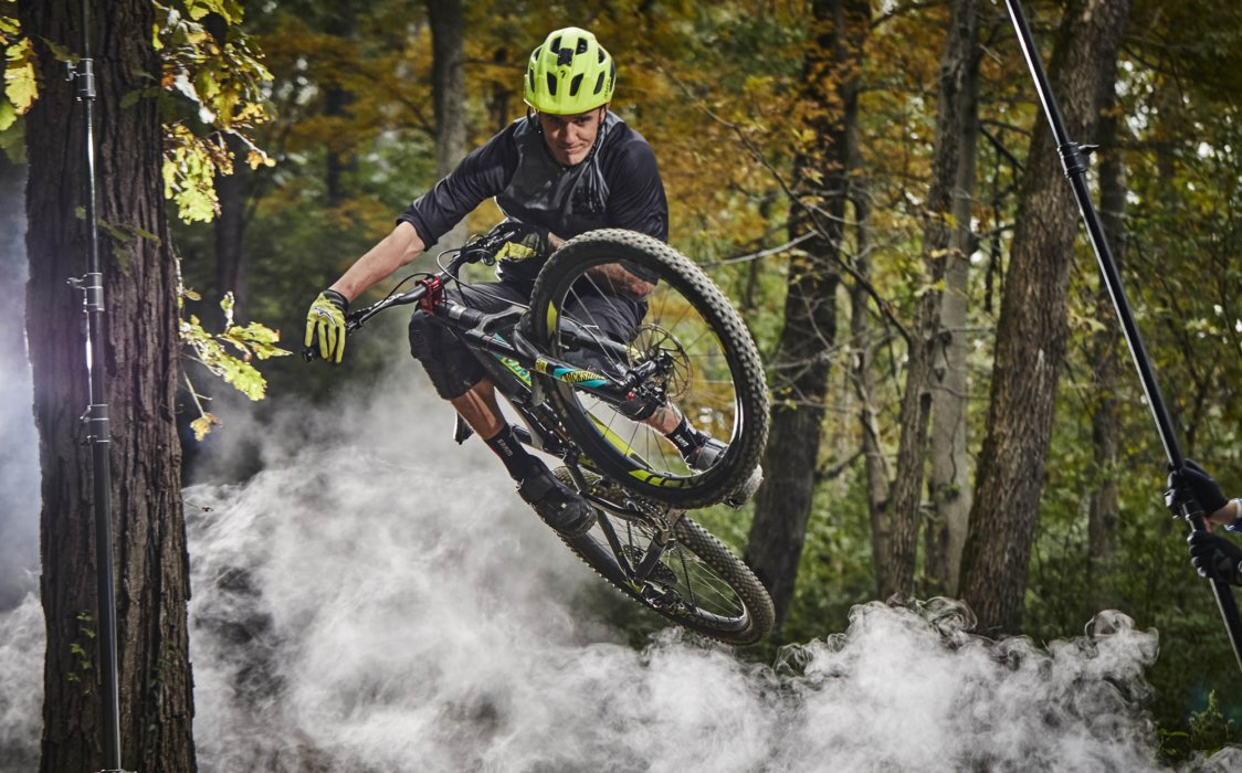A cyclist doing a trick jump in the woods with smoke