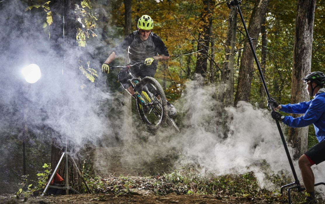 A cyclist doing a trick jump in the woods with smoke and you can see the set