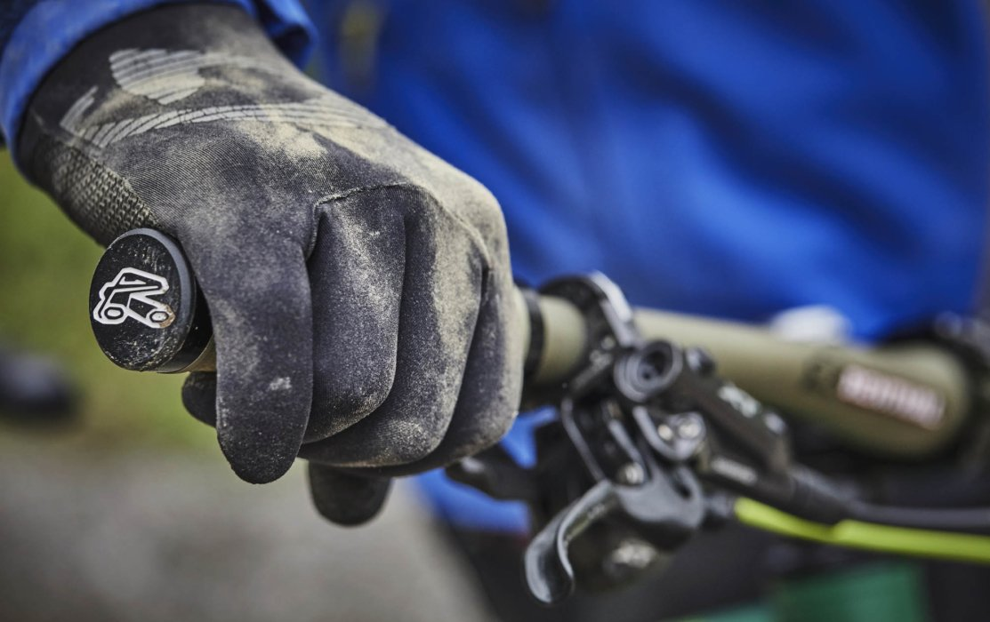 A bikers hand with gloves on bike's brakes