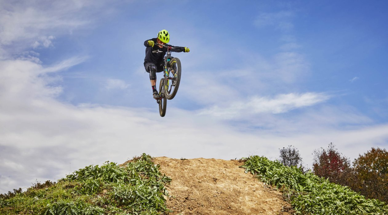 Cyclist dirt bike jumping over a hill