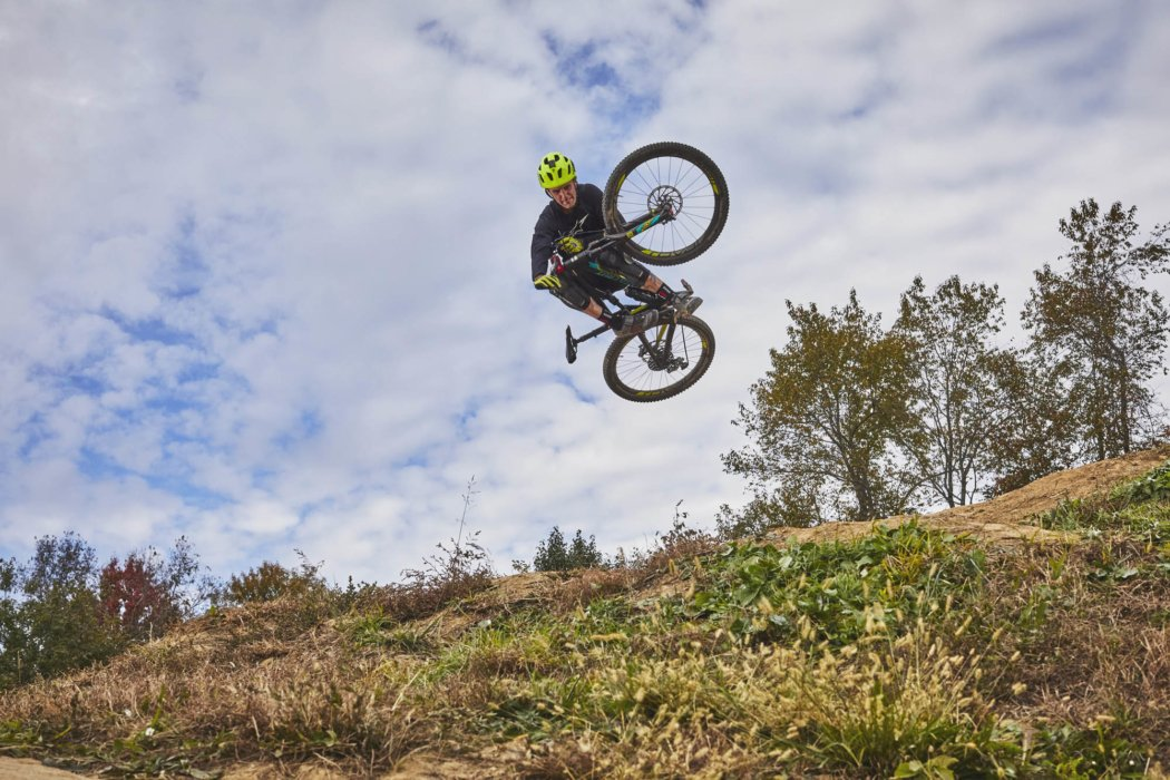 A cyclist doing a trick in the air on jump