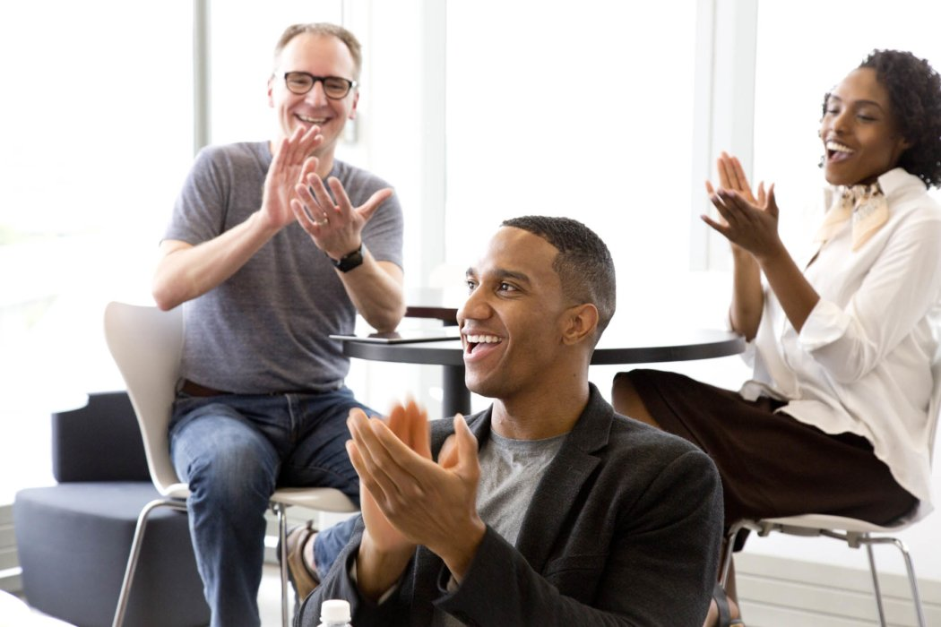 A group of people clapping in a meeting
