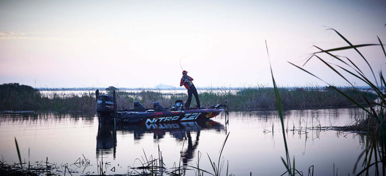 A man named KVD fishing on a boat with a rod and reel - outdoor photography
