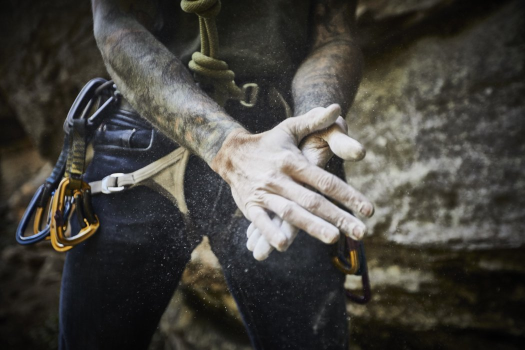 A male rock climbers hands with chalk getting ready for a climb