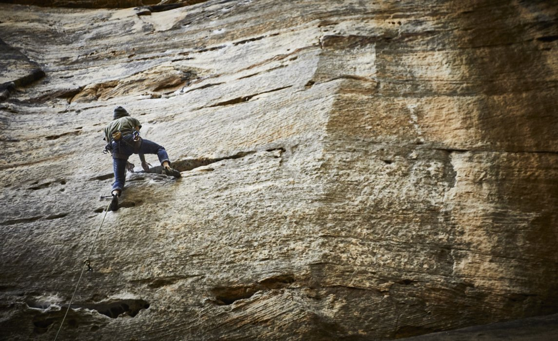 A male rock climber on a climbing a rock face