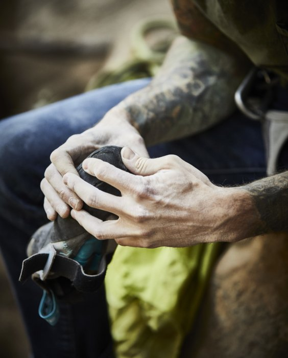A male rock climbers hands inspecting his shoes