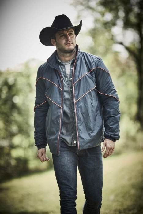 A man wearing rural cloth apparel and cowboy hat walking