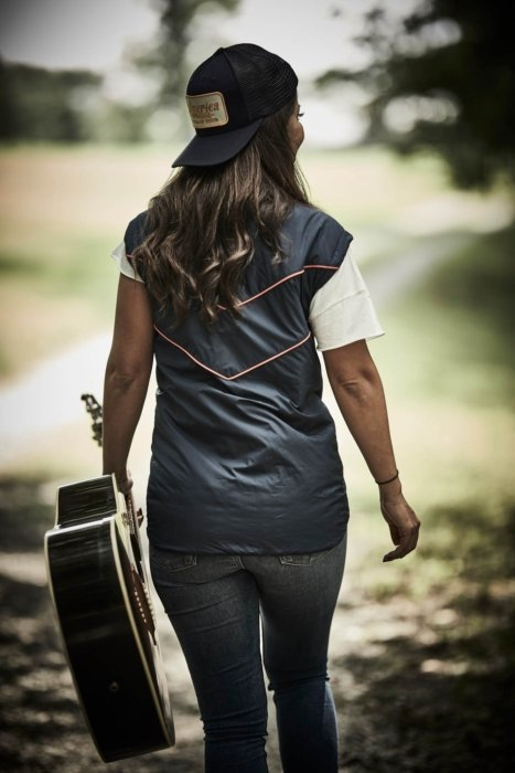 A woman walking with a guitar wearing rural cloth apparel
