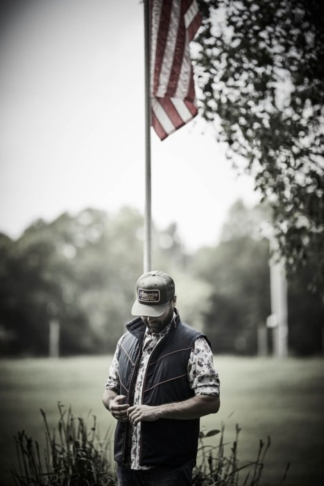 A man standing under an american flag wearing rural cloth apparel