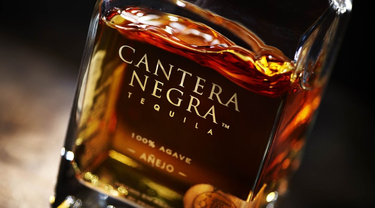 Bottle and liquid of amber anejo tequila - cantera negra -drink photography
