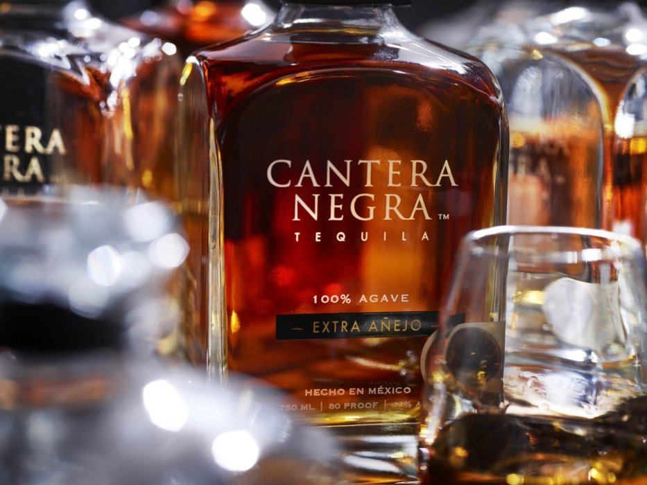 Bottles and glasses of Bottle amber extra anejo tequila - cantera negra -drink photography