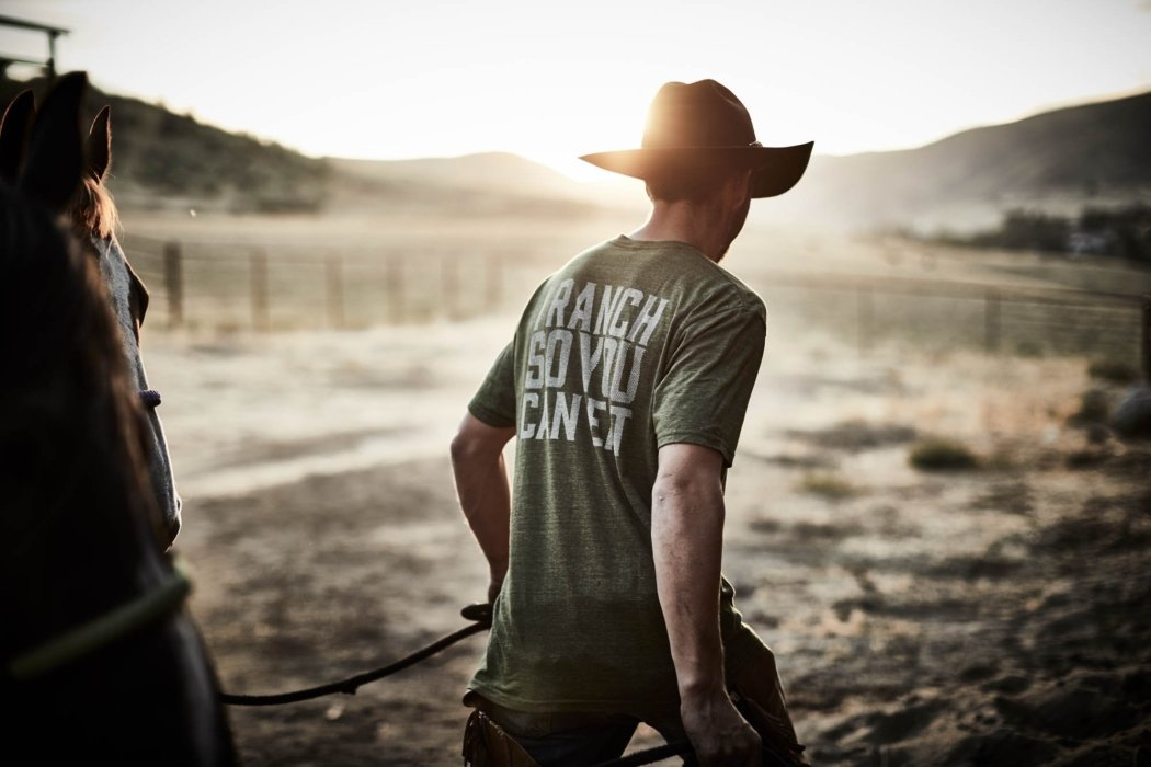 A man walking at sunset on ranch with horse - apparel photography