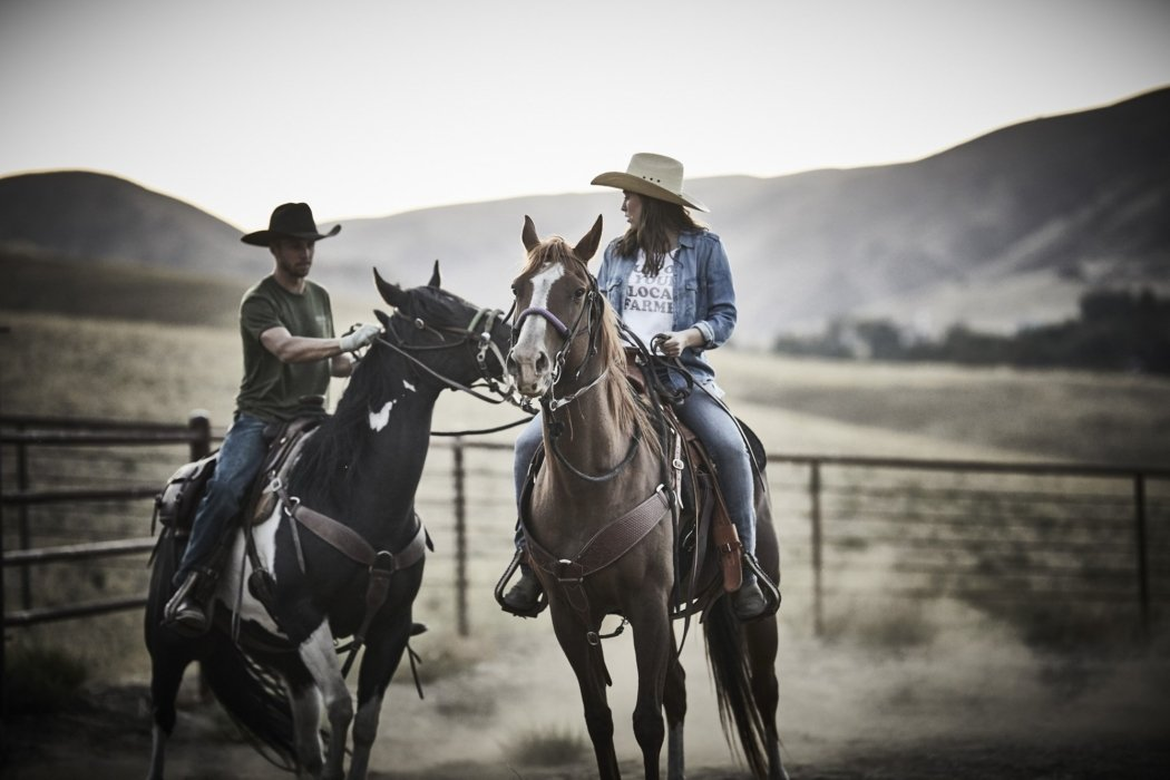 Two ranchers riding horses wearing rural cloth apparel