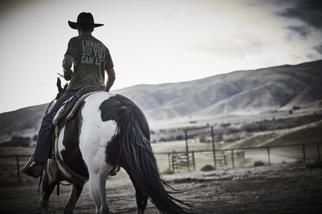 A rancher riding a horse wearing rural cloth apparel