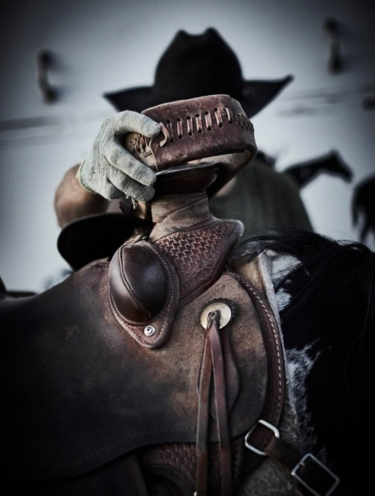 A man grabbing his saddle on a ranch - apparel photography