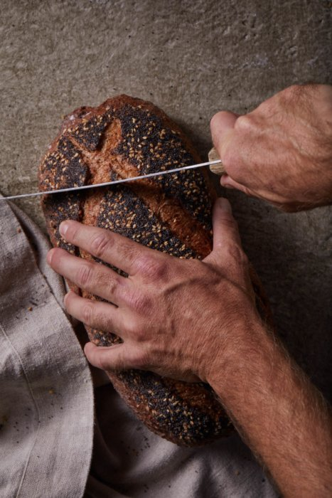 A loaf of seed artisan bread being sliced