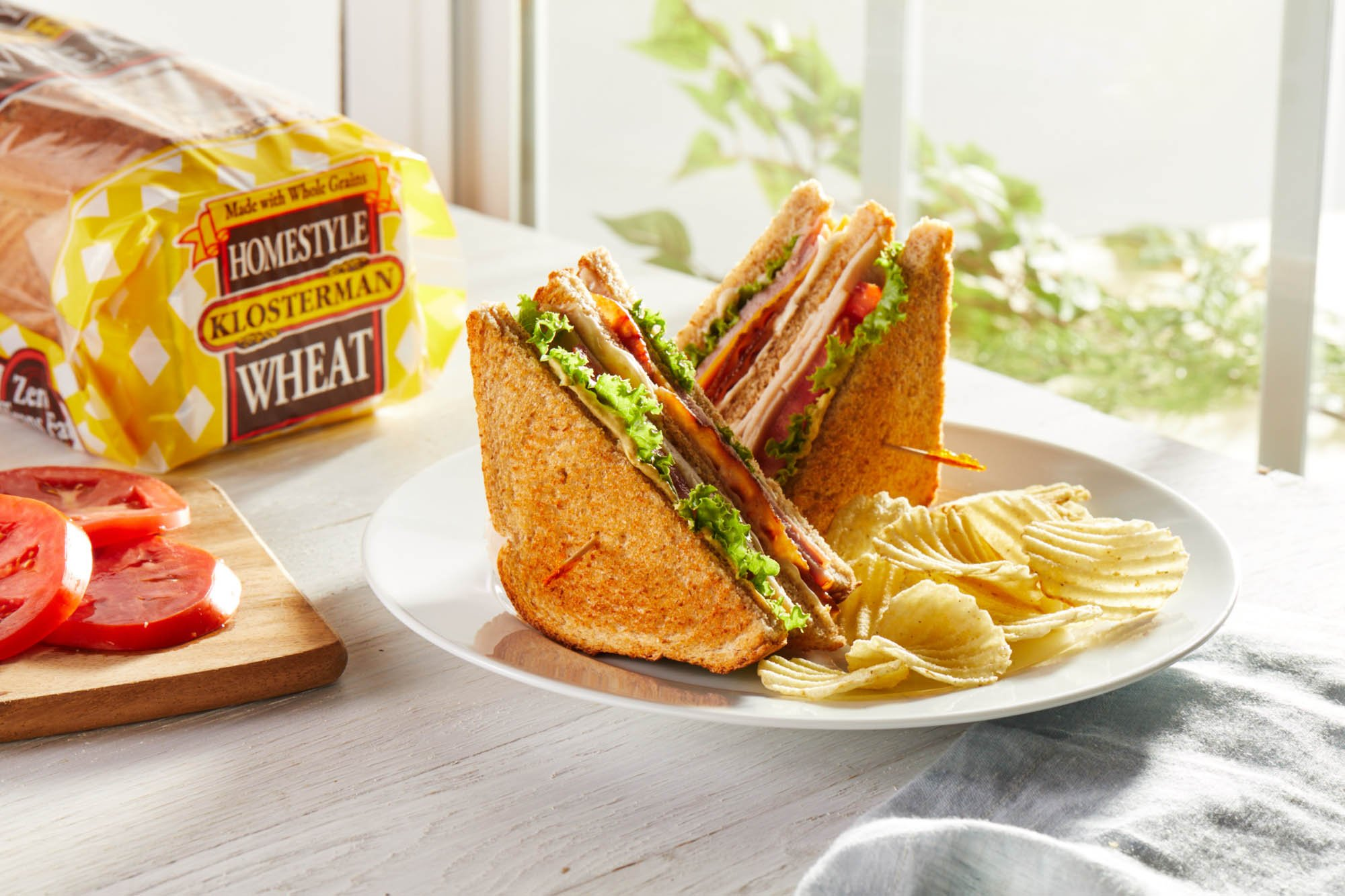 A beautiful double decker sandwich with chips and whole wheat bread