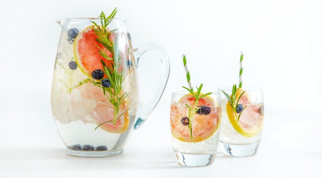 Fruit drinks in clear glasses on a white background