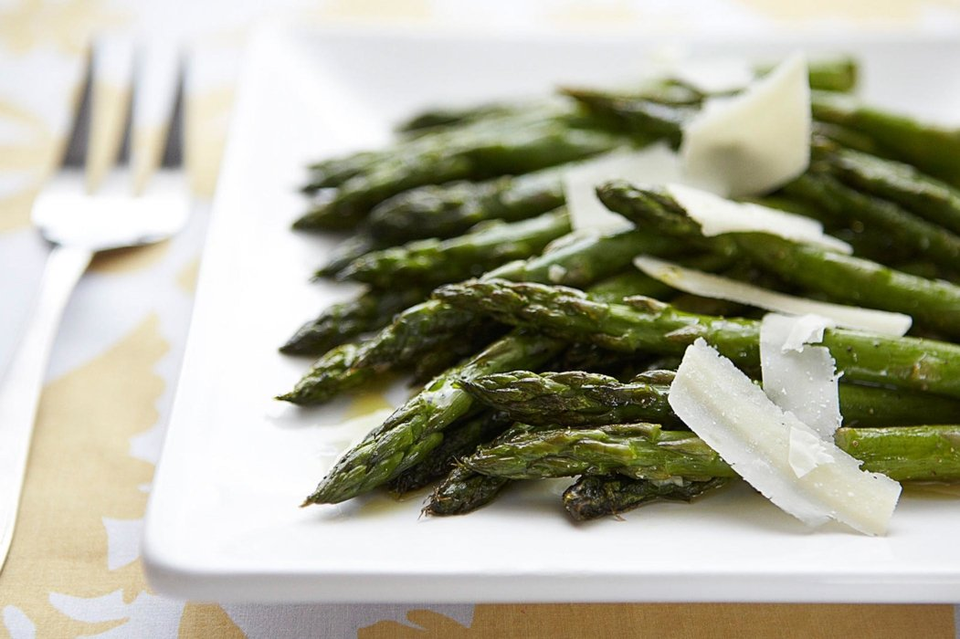 Asparagus with shaved parmesan on a white plate