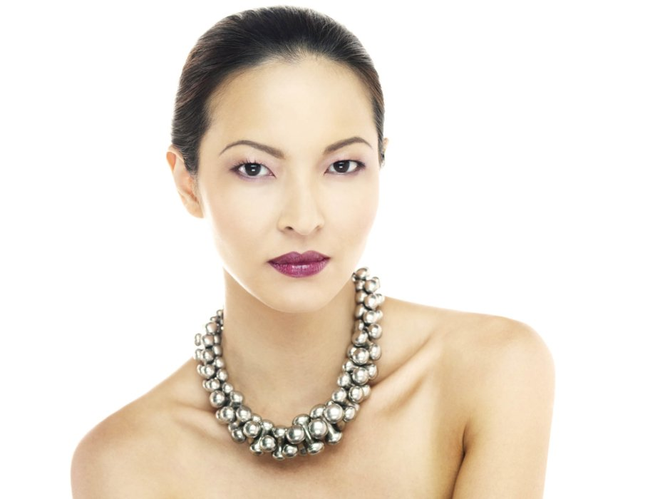 Beauty shot of a woman's face with makeup and a necklace