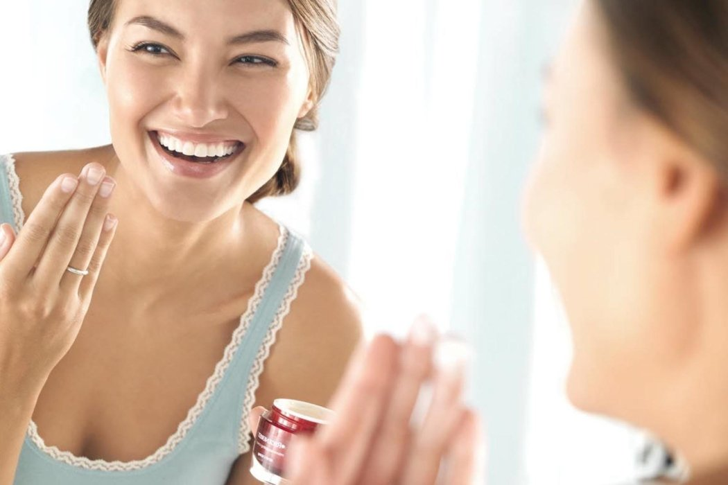Beauty shot of a woman laughing applying make-up