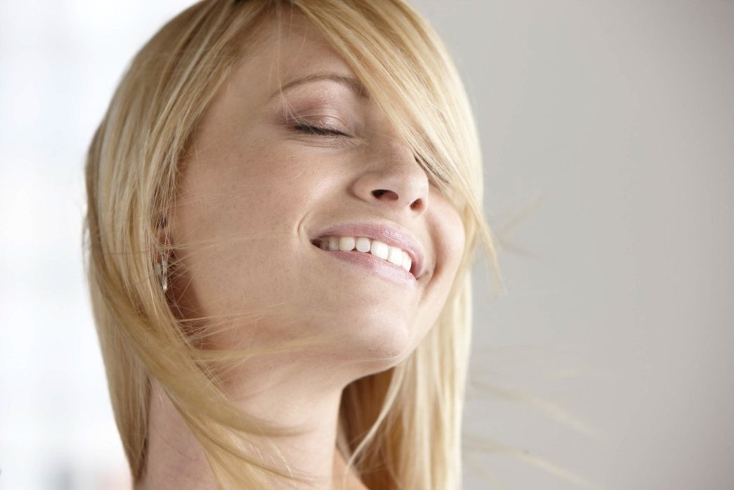 Beauty shot of a blond woman with ear rings smiling