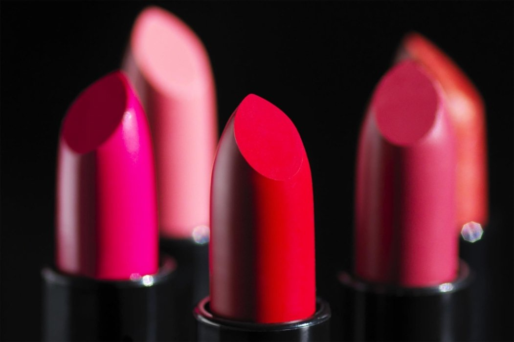 Close up on red lipstick cosmetics on a black background - Cosmetics photography