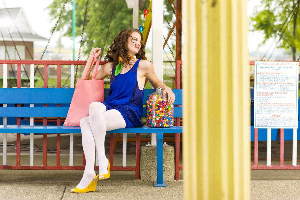 A female fashion model out doors with lots of colors on a bench