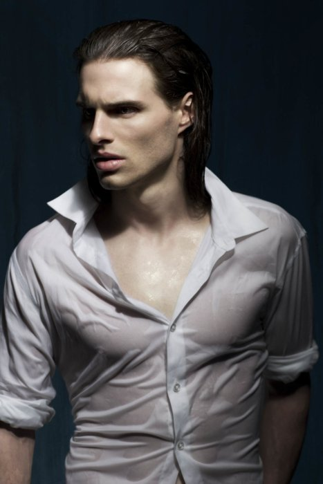 A male fashion model in a wet white shirt and long hair