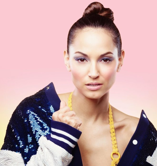 A female fashion model on a pink background with make-up facing camera