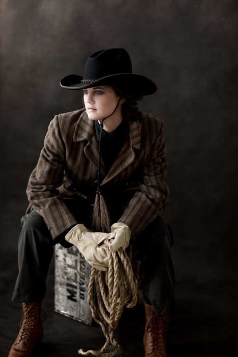 A female fashion model holding rope and a wearing western clothes