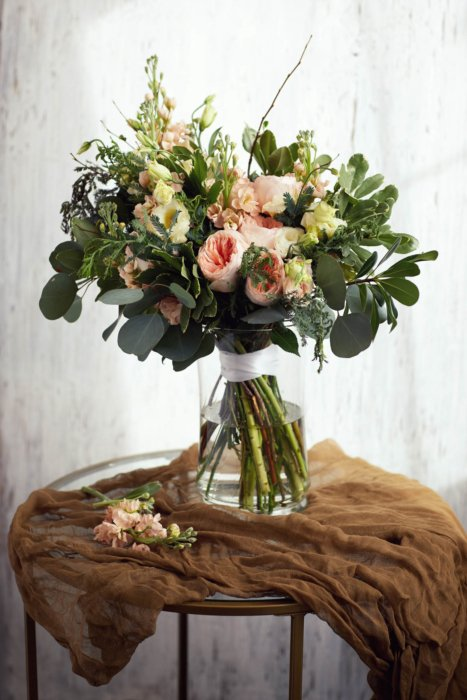 A beautiful flower arrangement in a vase on a brown cloth.