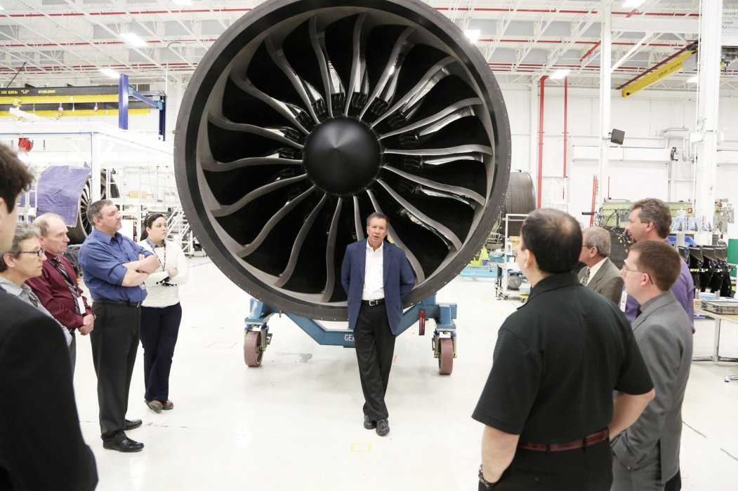 People around industrial airplane turbine