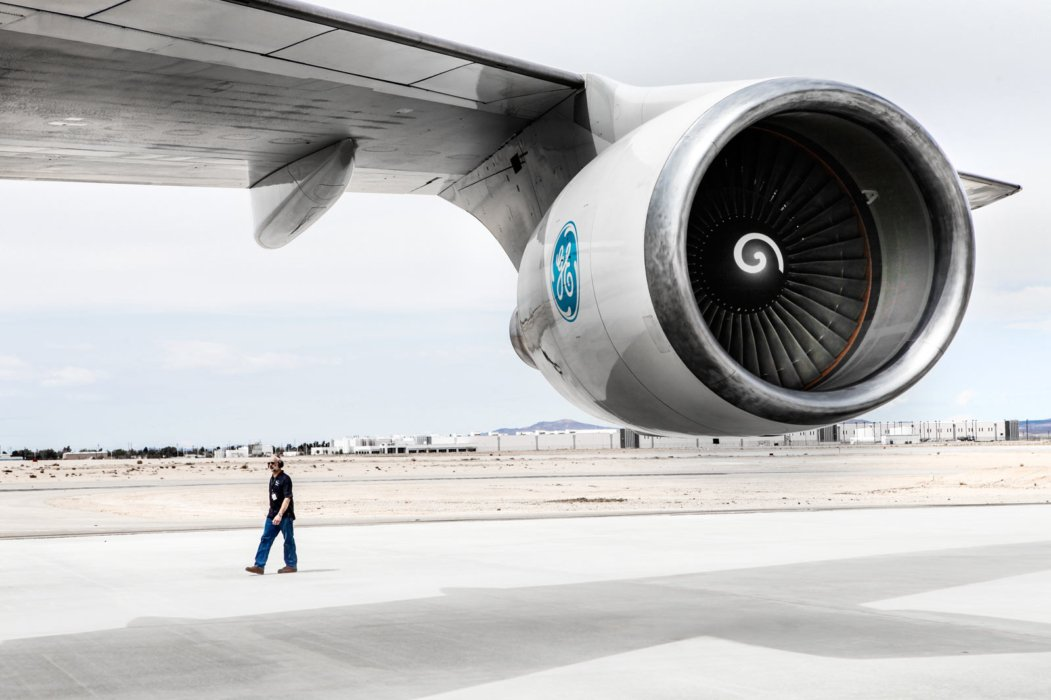 Person walking by GE built airplane engine