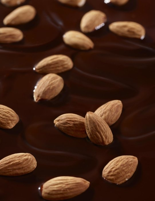 Almonds floating in melted chocolate