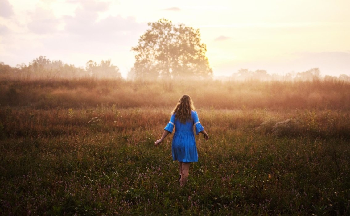 Woman in blue dress walking in a field