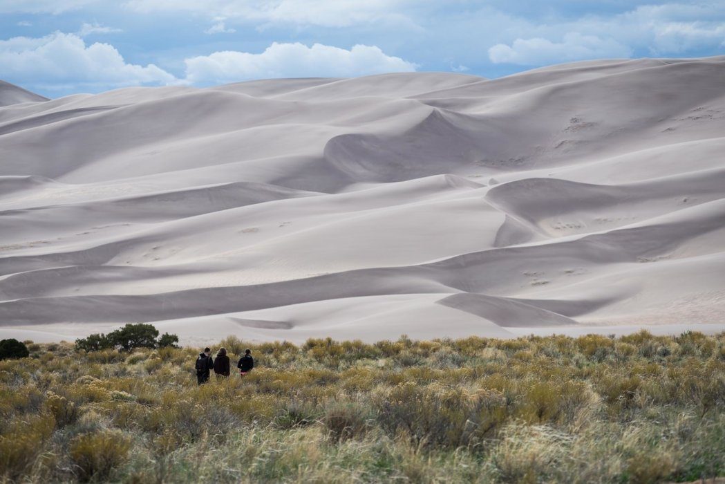 Travel photo of people approaching huge sand dunes