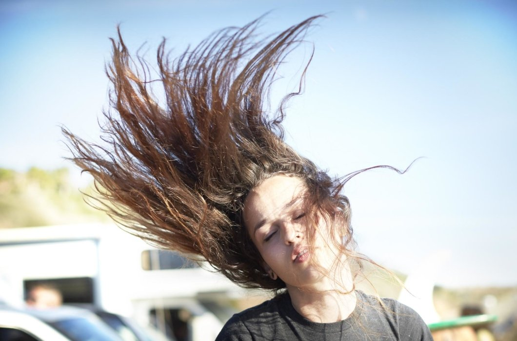 Lifestyle shot of a woman with her hair in the air - lifestyle photography