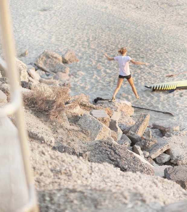 Lifestyle shot of a woman jumping on rocks on a beach - lifestyle photography