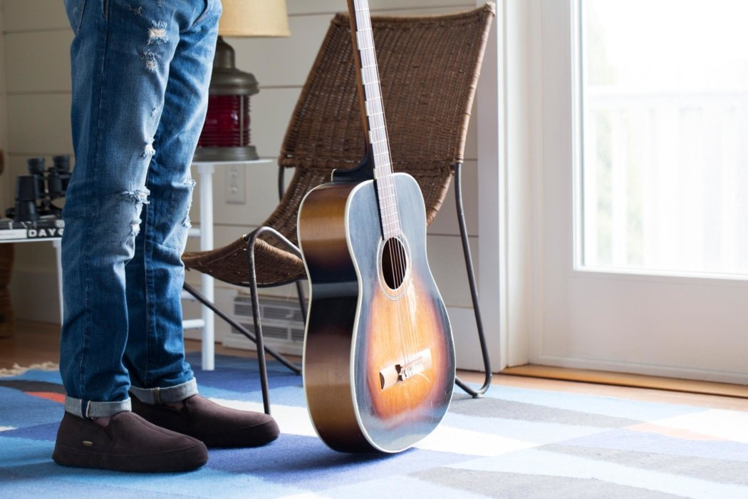 Lifestyle shot of slippers next to a guitar