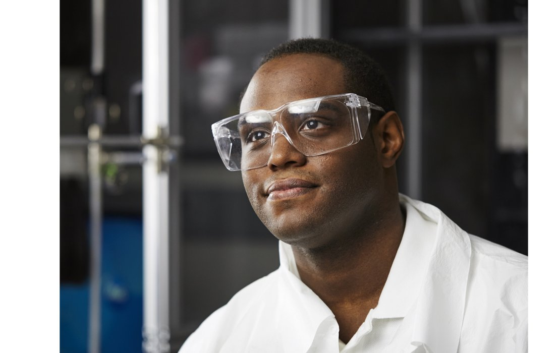 A man with safety glasses and lab coat