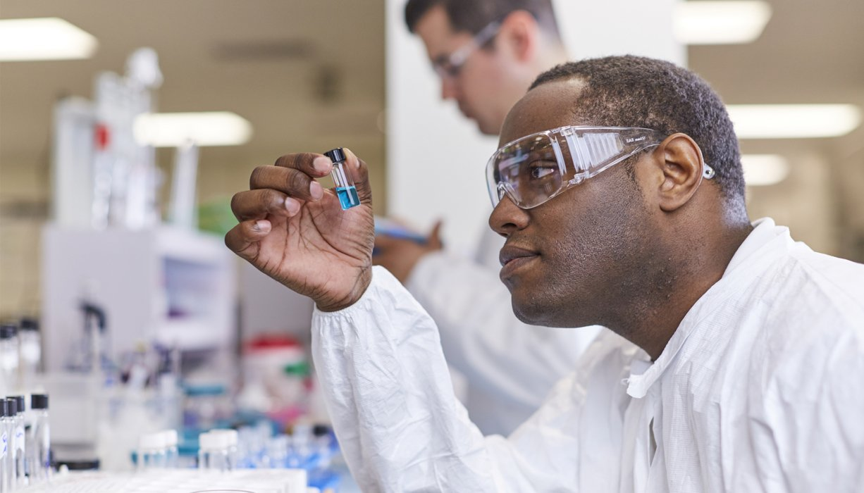 Close up on a man in a lab looking at a vial