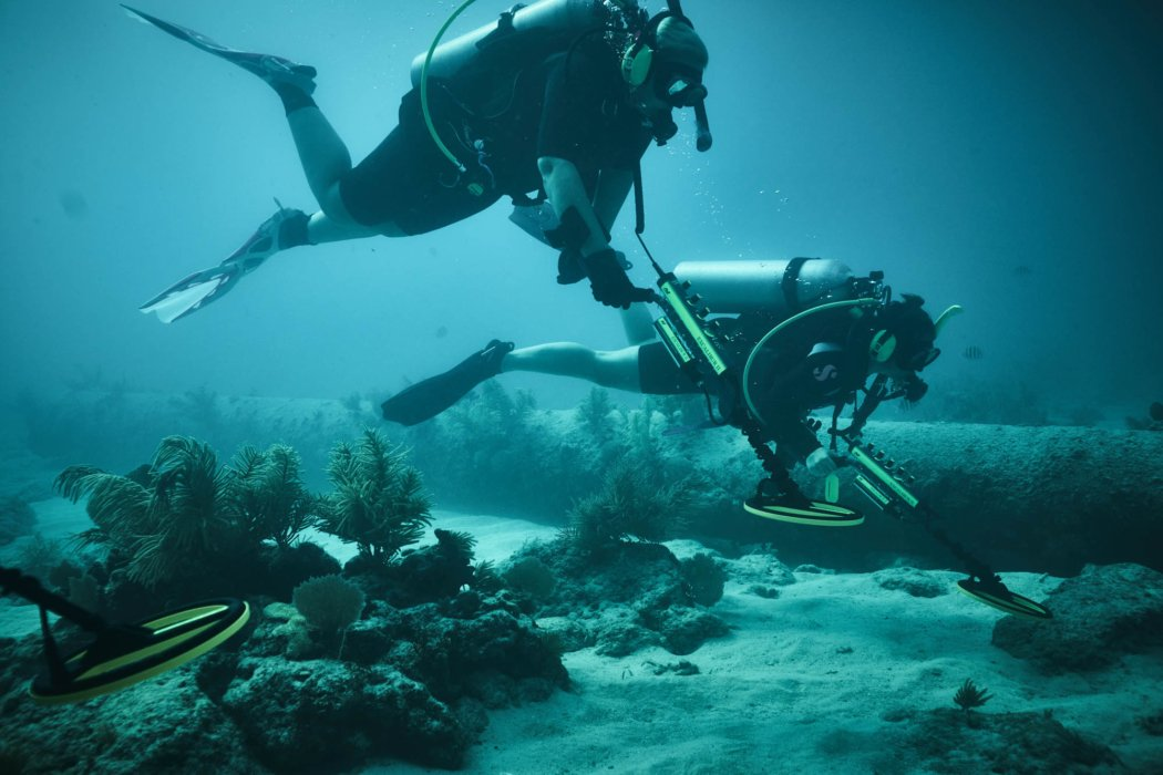 men in scuba gear diving under water with metal detectors