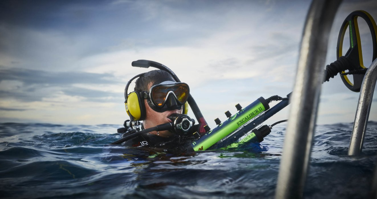 A diver ready to dive holding a metal detector at the surface